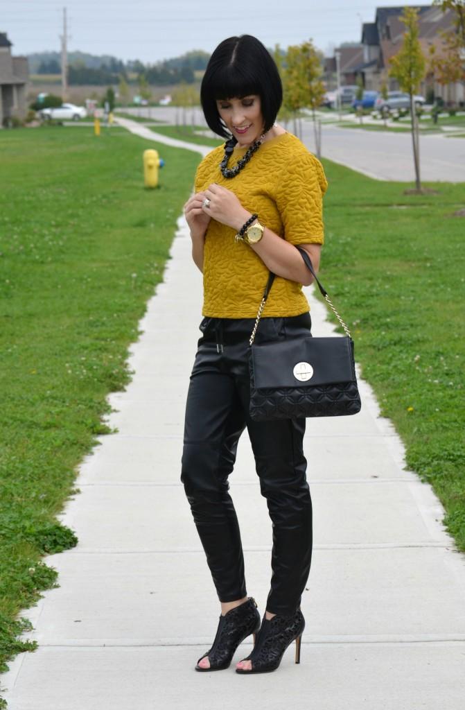 Black Leather, Faux leather pants, handbag, black purse, statement necklace, gold watch, mustard shirt, joggers, black booties