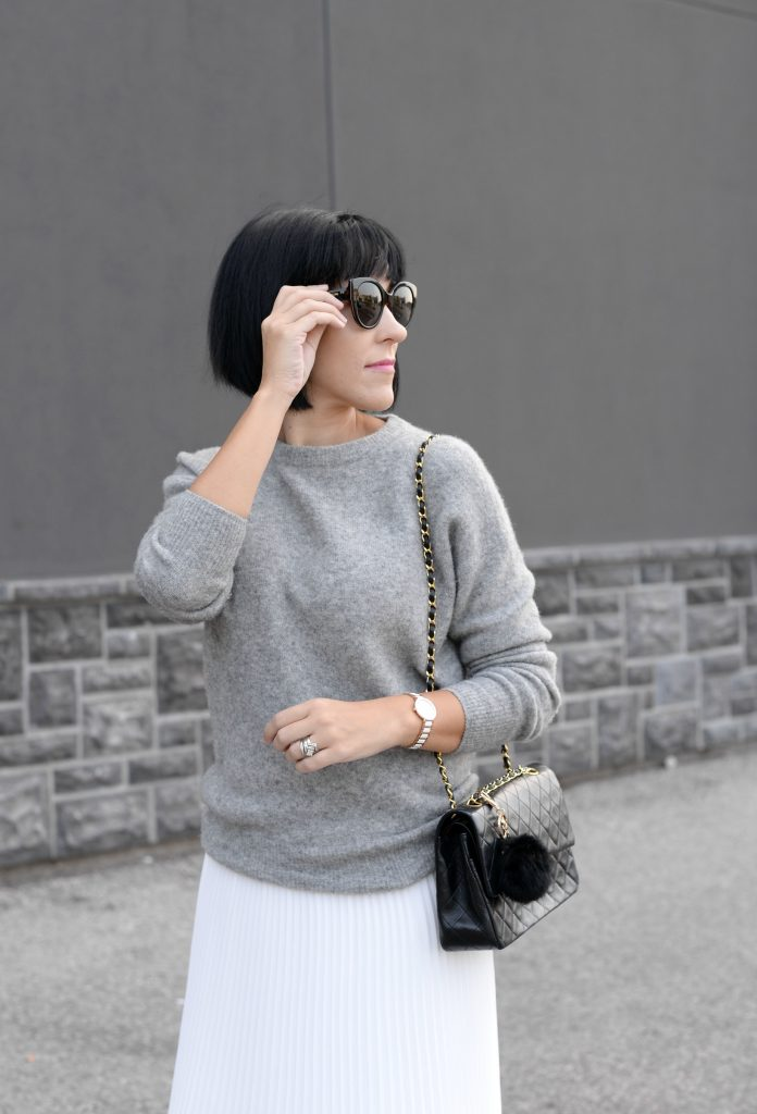 Pleats Are Back, spring skirt, what to wear this spring, grey Cashmere Sweater, Aritzia sweater, Chanel Double Flap, Bulova watch, toms Sunglasses, white Pleated Skirt, Aritzia skirt, Vince Camuto booties, black booties